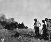 American soldiers looking at dead German pilot and wrecked plane